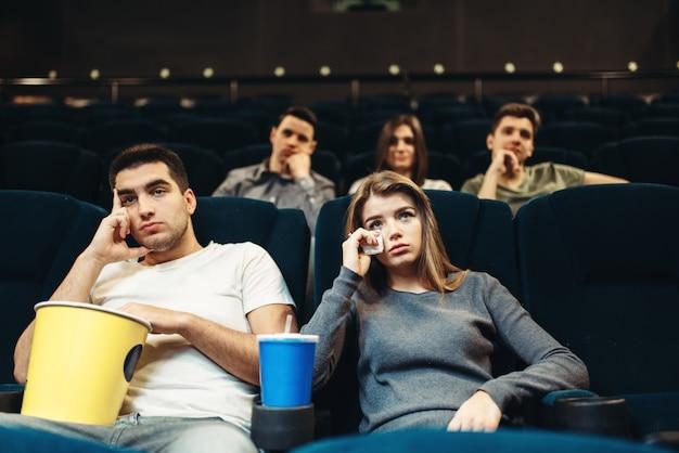 Мужчина и женщина с попкорном в кино. скучная концепция фильма, пара смотрит фильм