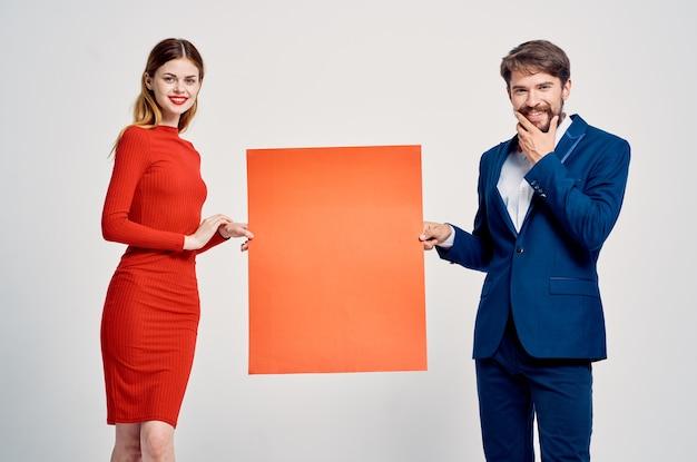 Мужчина и женщина с красным макетом, рекламная студия эмоций