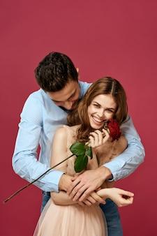 孤立した赤いバラを持つ男と女