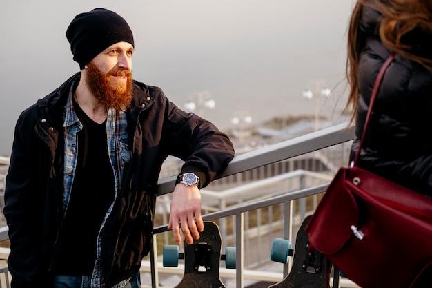 屋外でスケートボードを持つ男と女