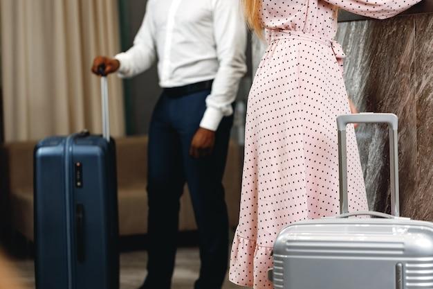 호텔 리셉션 근처에 서있는 가방을 가진 남녀