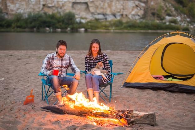 猫と男性と女性が火のそばに座っています