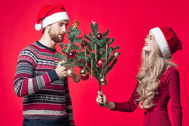 手に木を持つ男と女の休日のおもちゃの装飾赤い背景。高品質の写真