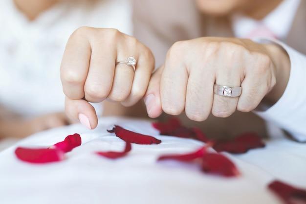 結婚指輪を持つ男性と女性。手をつないでいる若い夫婦、式典の結婚式の日。新婚カップルの手を結婚指輪で。