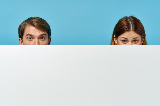 白いモックアップポスター広告サイン孤立した背景を持つ男性と女性。高品質の写真