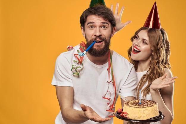 男と女の黄色の誕生日のお祝いケーキ