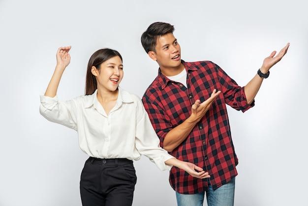 男性と女性はシャツを着て、喜んで手を横に伸ばしました