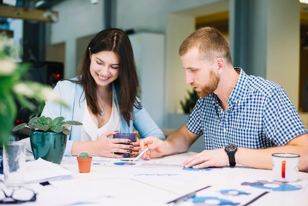 Мужчина и женщина, работающие на диаграммах вместе