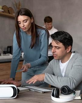 バーチャルリアリティヘッドセットとヘッドフォンでメディア分野で一緒に働く男性と女性