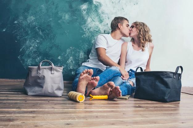 Мужчина и женщина молодая и красивая пара делают ремонт в новом доме счастливая молодая семья