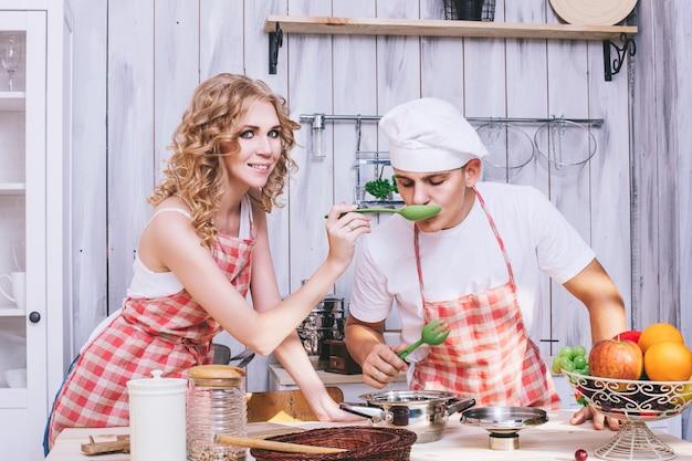 男と女の若くて美しいカップルがキッチンで料理をし、一緒に朝食をとり、助け合っています