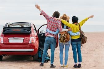 Man and women embracing near car on sea coast