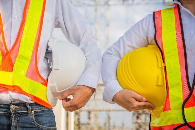ヘルメットの安全性を保持している男性と女性のエンジニア立っている屋外チームワーク管理プロジェクト