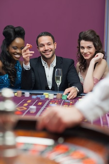 Man and women sitting at roulette table smiling