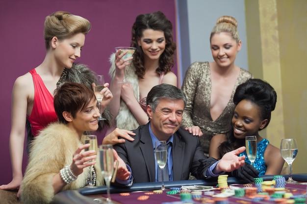 Мужчина и женщины, сидящие за столом, играя
