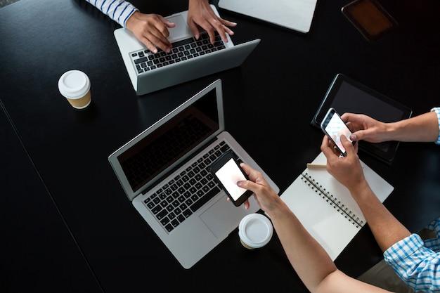 携帯電話とラップトップを使用している男性と女性