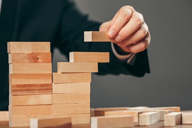 Человек и деревянные кубики на столе. концепция управления