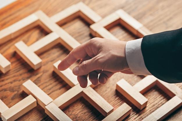 男とテーブルの上の木製キューブ。経営コンセプト