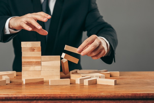 男とテーブルの上の木製キューブ。経営理念