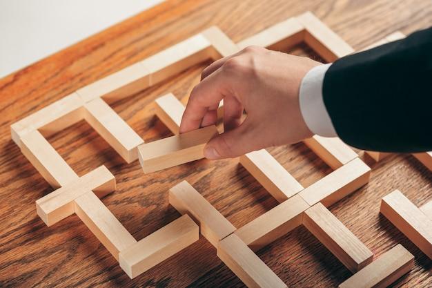 남자와 테이블에 나무 큐브입니다. 관리 개념
