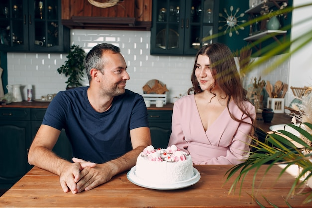 男と若い女性はテーブルの上にケーキと一緒に家庭の台所に座っています。