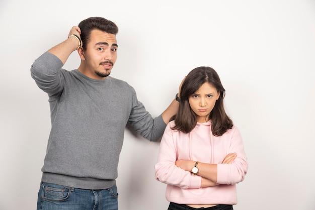 Uomo che chiede scusa alla sua ragazza pazza su bianco.