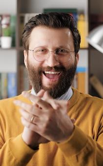 남자 박수. 수염을 기른 잘생긴 남자는 안경을 쓰고 카메라를 보고 행복하게 손바닥을 치며 웃고 있습니다. 클로즈업 보기