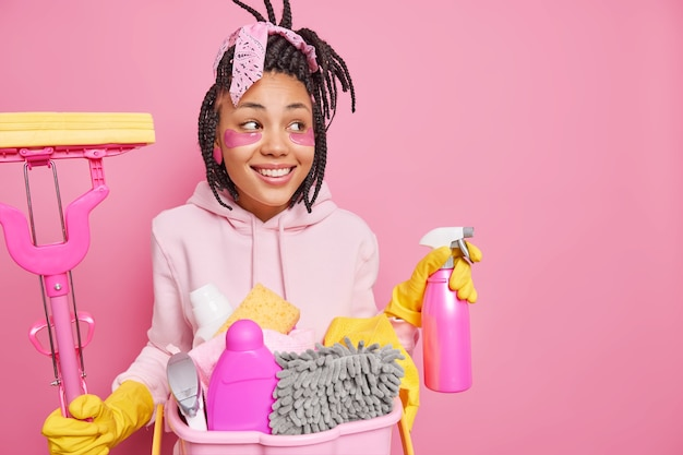 Man applies beauty patches holds mop and cleaning detergent cleans room uses chemical detergents looks aside poses on pink