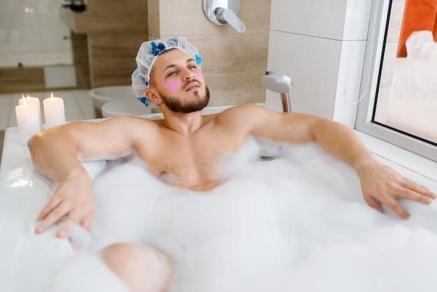 男はフェイスマスクを適用し、泡、朝の衛生状態でお風呂に横たわっています。男性はバスルーム、肌、体のトリートメント手順でリラックス