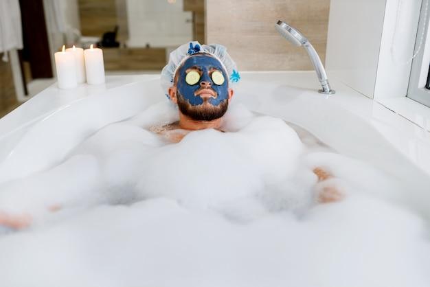 男性はフェイスマスクを適用し、泡、朝の衛生状態でお風呂でリラックスします。浴室、皮膚および体の治療手順で休んでいる男性