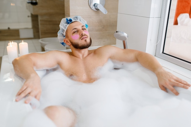 Man applies face mask and lies in bath with foam, morning hygiene. male person relax in bathroom, skin and body treatments procedures