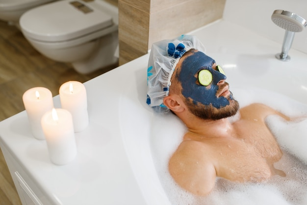 Man applies face mask and relax in bath with foam, morning hygiene. male person resting in bathroom, skin and body treatment
