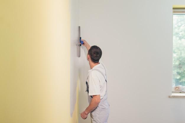 Мужчина шпателем наносит шпаклевку на стены в квартире делает ремонт