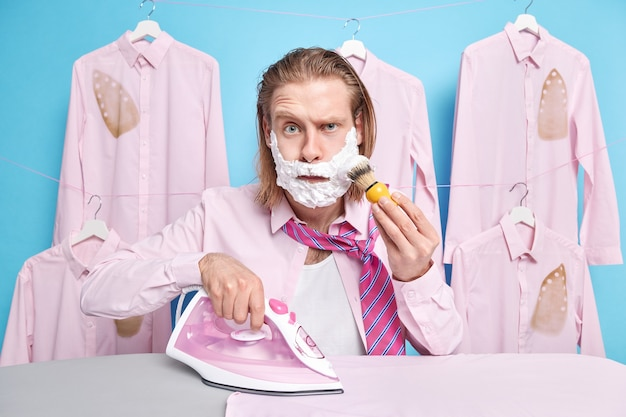 Man applies shaving gel on cheeks and raises eyebrows wears shirt and tie irons clothes prepares for party being at home