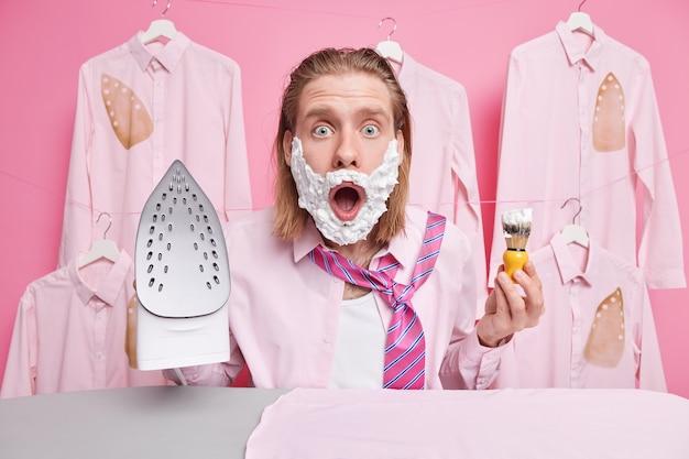 男は頬にシェービング ジェルを塗る アイロン 服 仕事用の服 ショックを受けて夜更かしする 電気アイロンを保持する夫の専業主婦が家事をしている