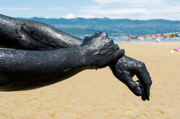 黒の癒しの粘土を適用する男