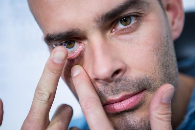 Man applying contact lens