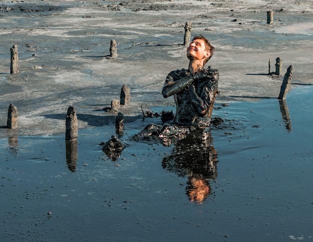 彼の体に治療の泥を適用する男