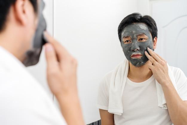 バスルームの鏡に顔のマスクを適用する男