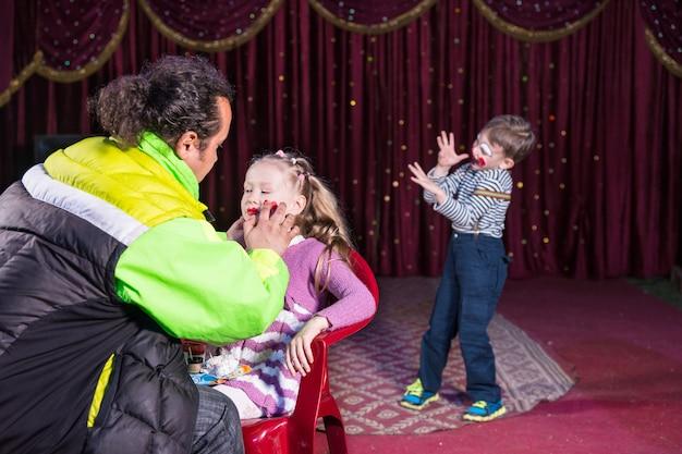 若い男の子のピエロがバックグラウンドでステージで実行しながら椅子に座っているブロンドの女の子の顔にメイクアップを適用する男