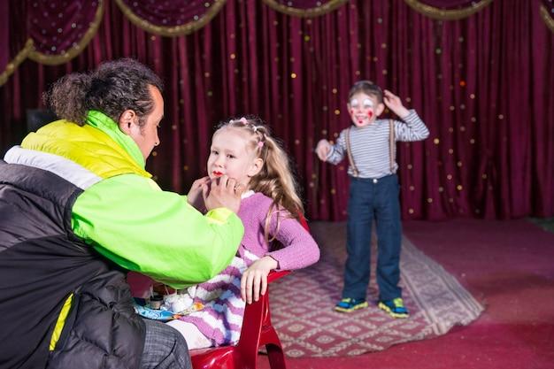 赤いカーテンでステージのバックグラウンドで実行している若い男の子のピエロと椅子に座っているブロンドの女の子の顔にメイクを適用する男