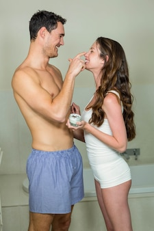 Man applying moisturizer on woman's face in bathroom