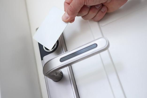 Человек, применяя пластиковую карту к дверному замку, чтобы открыть крупным планом