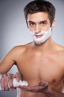 Человек, применяющий крем для бритья. красивый молодой человек без рубашки, наносящий крем для бритья на лицо и смотрящий в камеру, стоя изолированным на сером фоне