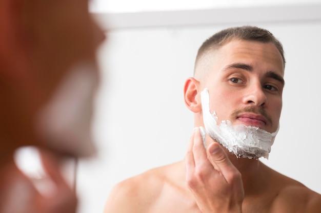 Человек, применяя пену для бритья в зеркале