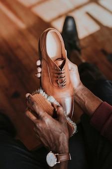 彼の茶色の革の靴に靴磨きを適用する男