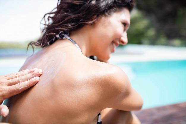 Man applying sunscreen on back of her womanânear pool on a sunny day
