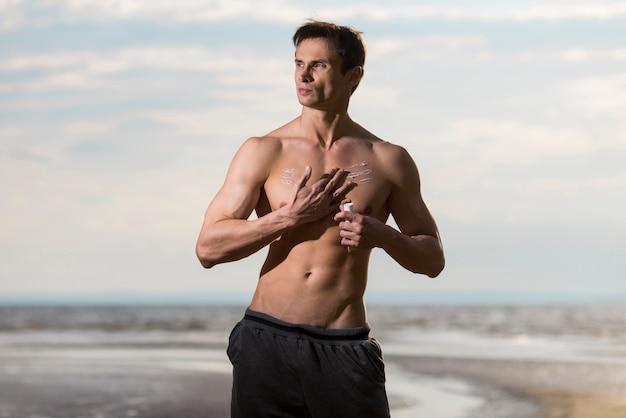 海岸で日焼け止めローションを適用する男 無料写真