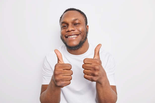 Man approves incredible promo keeps thumbs up likes and agrees being satisfied with something wears casual clothes praises cool job isolated on white