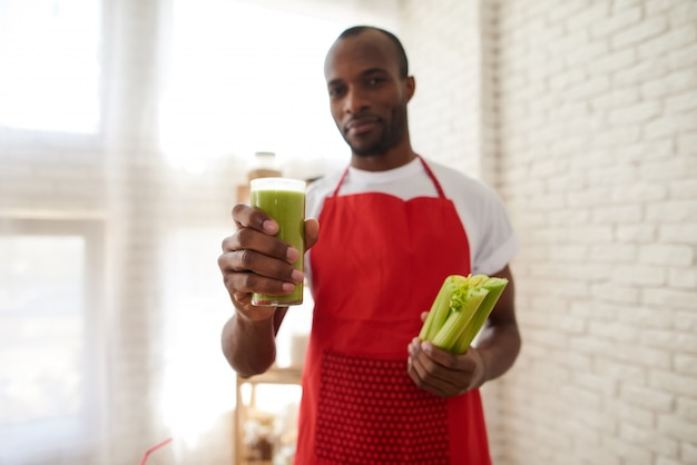 Man in apron holds glass of fresh celery juice at kitchen.